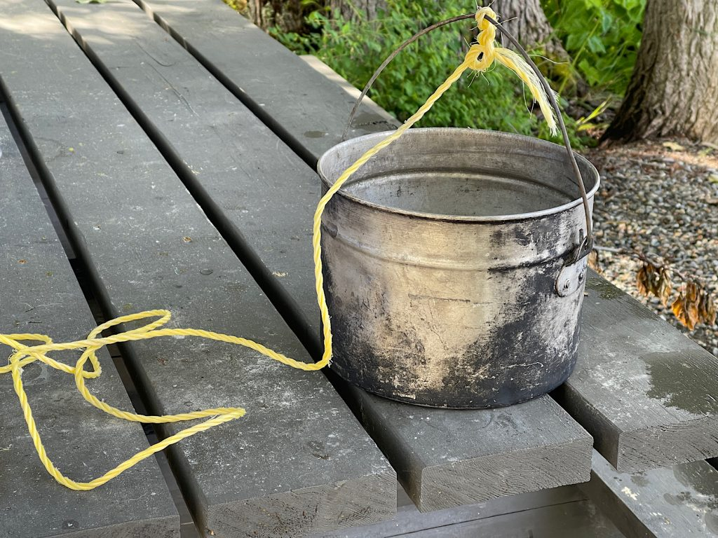 A camping pot with a rope tied to the handle
